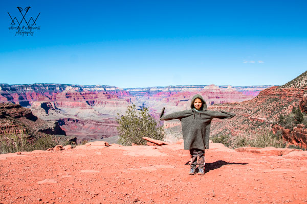 little kid arms open by grand canyon